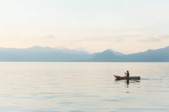 A local paddling on the still waters of the lake in a canoe made of wooden planks.