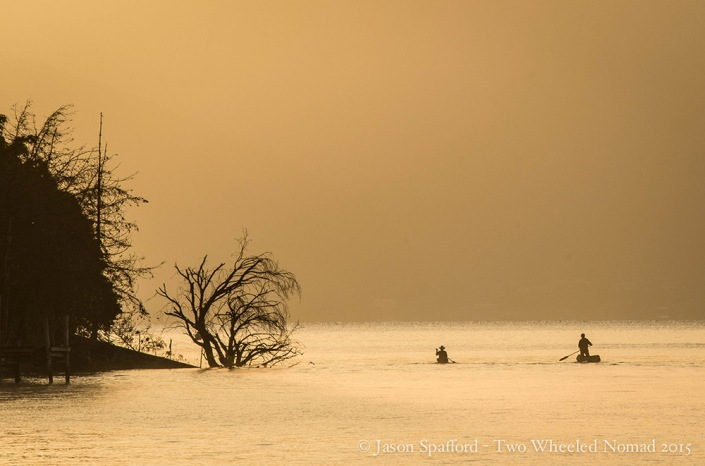 Locals paddling in dugout canoes on Lake Atitlán, San Marcos La Laguna, Guatemala.