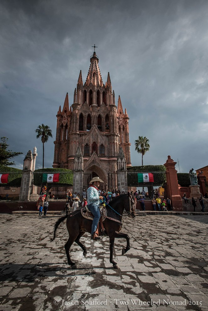 Show horse trotting with a showmanship's grace diagonally across the cobble stones in front of the uniquely constructed parish church
